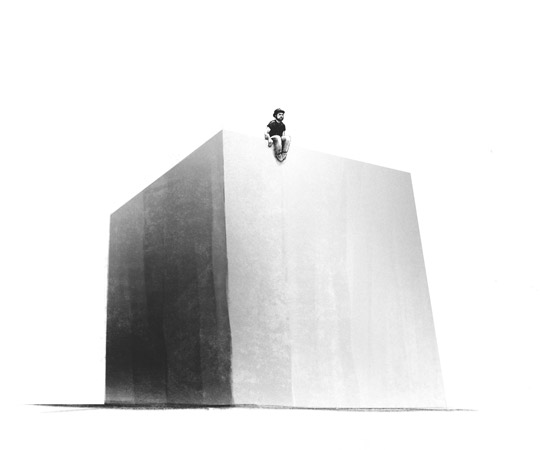 Lonely man on top of huge cube
