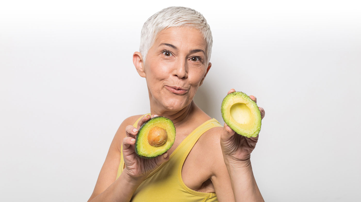 Older woman holding Avocados